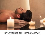young man relaxing on massage... | Shutterstock . vector #596102924