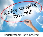 Small photo of Woman Hand Writing We Are Accepting Bitcoins with black marker on visual screen. Isolated on Sunny Sky. Business concept. Stock Photo