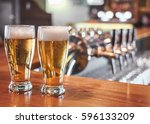two  glasses of beer on a bar... | Shutterstock . vector #596133209