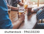 hands holding glasses with beer ... | Shutterstock . vector #596133230