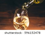 pouring white wine from a... | Shutterstock . vector #596152478