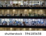 Small photo of Office skyscraper windows with people working within at night
