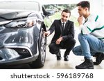 Small photo of Young car salesman showing the advantages of the car to the customer and tires.