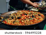 large pan of paella in a street ... | Shutterstock . vector #596495228