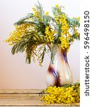 Small photo of Still life with yellow spring flowers. Acacia dealbata known as silver wattle, blue wattle and mimosa. Bouquet in vase on wooden table on smooth bright background.
