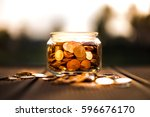 coins in glass on the wooden... | Shutterstock . vector #596676170