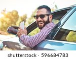 happy male driver smiling while ... | Shutterstock . vector #596684783
