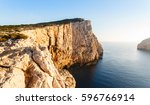 Small photo of high cliffs and SEA in the sun at sunset, Neptune's Grotto in Sardinia, Italy