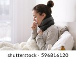 young ill woman in bed at home | Shutterstock . vector #596816120