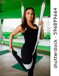 Small photo of portrait young women making antigravity yoga exercises. Aerial aero fly fitness trainer workout. white hammocks, eco green background studio. interior mirrors. meditates. harmony and serenity concept