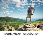 tourist on the peak of high... | Shutterstock . vector #597029354