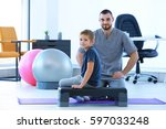 physiotherapist and little boy... | Shutterstock . vector #597033248