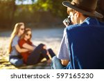 Small photo of Hipster men in the hat takes pictures of his girlfriends. A group of friends enjoying time on the beach. They laugh and smile. Friendly atmosphere. Guys enjoy photos. Well spend the summer.