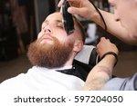 hairdresser shaving client in...   Shutterstock . vector #597204050