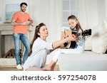 happy father looking at mother... | Shutterstock . vector #597254078