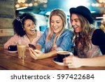 three young women at wooden... | Shutterstock . vector #597422684