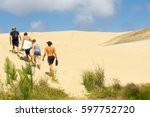 Small photo of TE PAKI, NEW ZEALAND - FEBRUARY 14; Young people head off climbing Te Paki Sand Dunes, enormous white dunes a favorite tourist attraction and fun place February 14, 2017 Te Paki New Zealand