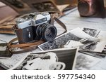 Small photo of An old film camera and family album on a white wooden background among vintage families photos