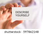 Small photo of Closeup on businessman holding a card with DESCRIBE YOURSELF message, business concept image with soft focus background