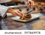 chef in restaurant arrangin and ... | Shutterstock . vector #597869978