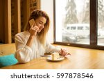 a girl is sitting in a cafe and ... | Shutterstock . vector #597878546
