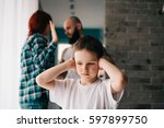 sad child covering his ears... | Shutterstock . vector #597899750
