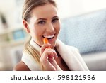 fit woman eating carrot at home | Shutterstock . vector #598121936