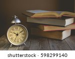 Small photo of Roman Numeral in Vintage Alarm Clock and Open Book Background with Copy Space for Advertise about the Education or Nostalgia Concept