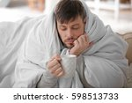 young ill man drinking hot tea... | Shutterstock . vector #598513733