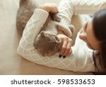 Stock photo young woman playing with cute cat at home 598533653