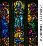 Small photo of BRUSSELS, BELGIUM - APRIL 18, 2009: Stained Glass in Koekelberg Basilica, Brussels, depicting God, the Holy Spirit, Jesus personified by the Agnus Dei, Joseph and Mary.