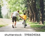 father help his son ride a... | Shutterstock . vector #598604066