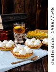 Small photo of Delicious homemade mini tarts (tartlets) with fruit kiwi and lemon kurd cream with meringue. Served with clear tea mug in cup holder and fruits slices. Tasty sweet small dessert and cake. Vertical.
