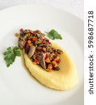 Small photo of rabbit offal stew in mashed potato decorated with parsley leafs