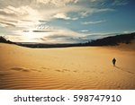 man walk alone over dunes in a... | Shutterstock . vector #598747910