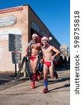 Small photo of ATLANTA, GA, USA - DECEMBER 10, 2016: Two male runners wearing speedo swimsuits jog down a city street at the Santa Speedo Run, an annual charity fundraiser, on December 10, 2016 in Atlanta, GA.