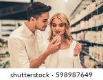 beautiful couple is choosing... | Shutterstock . vector #598987649