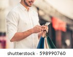 handsome guy with shopping bags ... | Shutterstock . vector #598990760