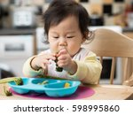 baby eating vegetable at home | Shutterstock . vector #598995860