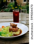 Small photo of Lamb shank with vegetables on an pub outdoor wooden table, glass of water and juice next to it