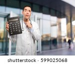 surprised young doctor using a... | Shutterstock . vector #599025068