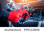 Small photo of Accumulator charging. Hands and terminals. Car repair. Service station.