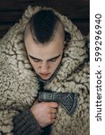 Small photo of Viking portrait, strong handsome viking warrior with steel axe ritual before battle, thor cosplay, scandinavian historical costume clothes, ancient warrior with mohawk face close-up