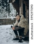Small photo of strong viking warrior sharpening his weapon near wooden hut in scandinavian forest in the winter, thor cosplay costume, northern lumberjack with mohawk hairstyle sitting with axe, viking concept