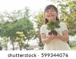 kid holding young plant in... | Shutterstock . vector #599344076