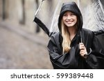 beautiful woman smiling in rain | Shutterstock . vector #599389448