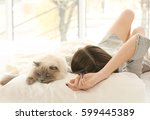 Stock photo beautiful young woman with cute cat resting at home 599445389