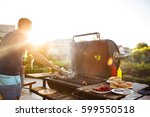 young men roasting barbecue on... | Shutterstock . vector #599550518