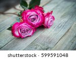 pink roses on wooden background.... | Shutterstock . vector #599591048