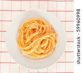 A plate of spaghetti pasta on a checked tablecloth with tomato sauce seen from above - stock photo